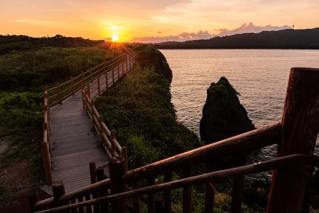 Vista dall'alto da una scala in legno. splendido sole che sorge alla fine del sentiero in legno con i suoi vibranti raggi di sole.