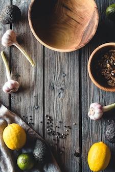 Vista dall'alto di frutta e verdura con ciotole sul tavolo di legno
