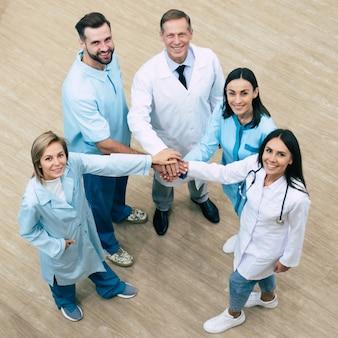 Foto a figura intera vista dall'alto del team di medici di successo felice durante la conversazione in ospedale