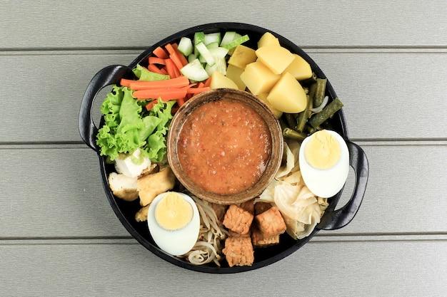 Vista dall'alto ingredienti gado-gado. gado gado è un'insalata di verdure tradizionale indonesiana servita con salsa di arachidi, popolare a jakarta. di solito servito con lontong (torta di riso indonesiano).