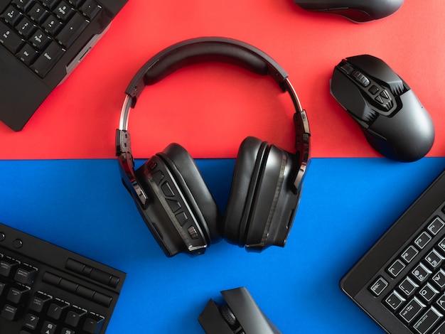 Vista dall'alto un equipaggiamento da gioco, mouse, tastiera, cuffie e tappetino per mouse sullo sfondo del tavolo.