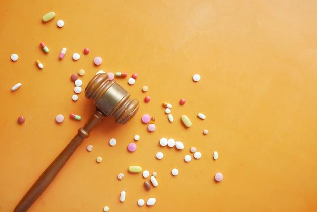 Vista dall'alto di martelletto e pillole mediche su sfondo arancione