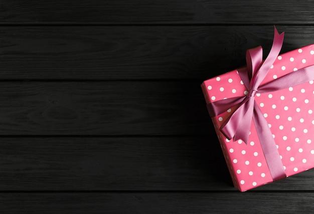 Vista dall'alto di una confezione regalo su una parete di legno nera, regali su una tavola nera un piatto laici, un concetto festivo