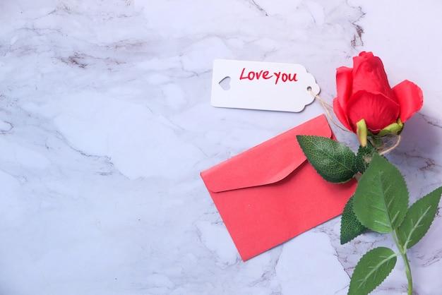 Vista dall'alto della busta del contenitore di regalo e del fiore di rosa su fondo bianco