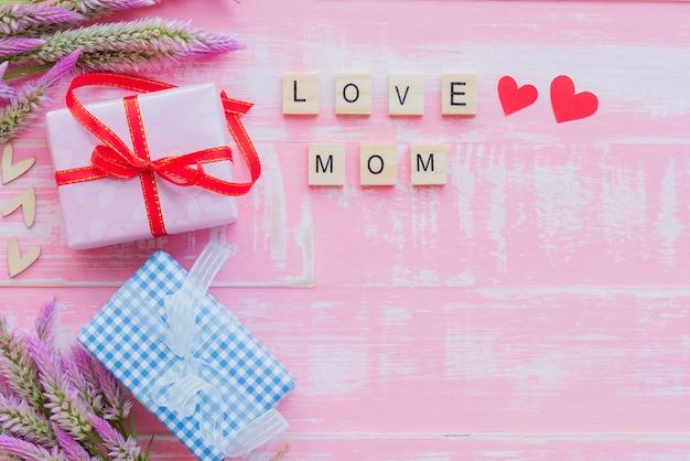 Vista dall'alto della confezione regalo con fiore e tag con ti amo testo di mamma sul blocco di legno
