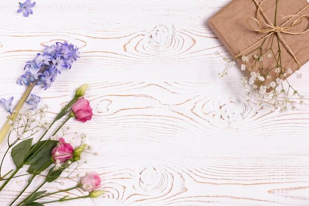 Vista dall'alto della confezione regalo avvolta in carta kraft, fiori blu e rosa sul tavolo bianco