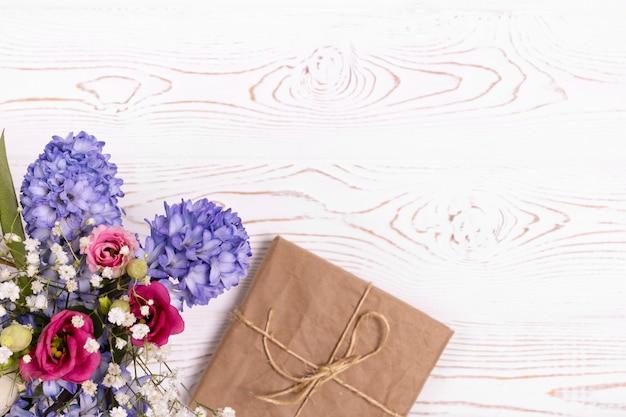 Vista dall'alto della confezione regalo avvolta in carta, fiori blu e rosa sul tavolo bianco
