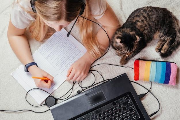 Vista dall'alto di una ragazza in cuffia usando il suo laptop e prendendo appunti sul suo taccuino con un gatto al suo fianco