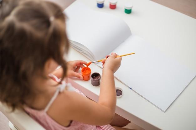 Vista dall'alto una ragazza dipinge a un tavolo