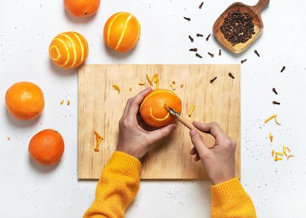 Vista dall'alto delle mani della ragazza intagliare ornamenti in un'arancia, vista dall'alto