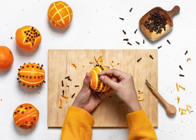 Vista dall'alto delle mani della ragazza che fanno ornamenti di chiodi di garofano su un'arancia, vista dall'alto
