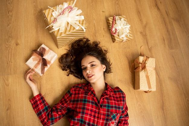 Vista dall'alto della ragazza. è sdraiata sul pavimento con i regali. natale. nuovo anno