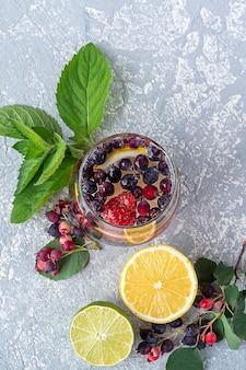 Vista dall'alto di un bicchiere di bevanda detox con frutti di bosco e limone su sfondo di cemento