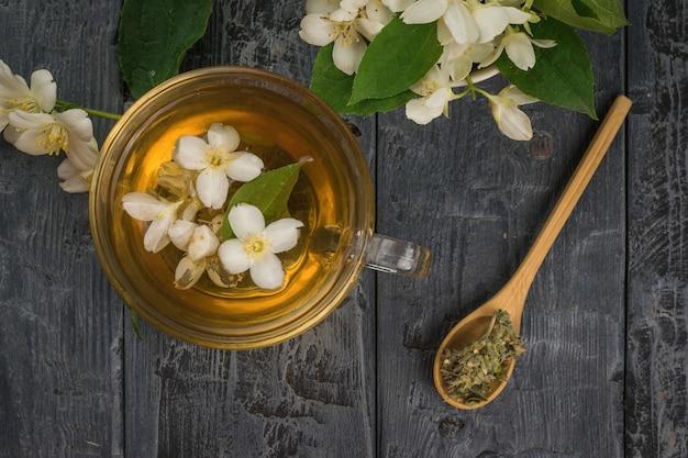Vista dall'alto di una teiera di vetro e un cucchiaio di tè al gelsomino. una bevanda tonificante che fa bene alla salute.
