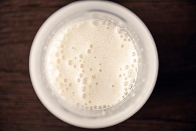 Vista dall'alto di un bicchiere con frullato alla vaniglia, cocktail schiumoso con schiuma e bolle and