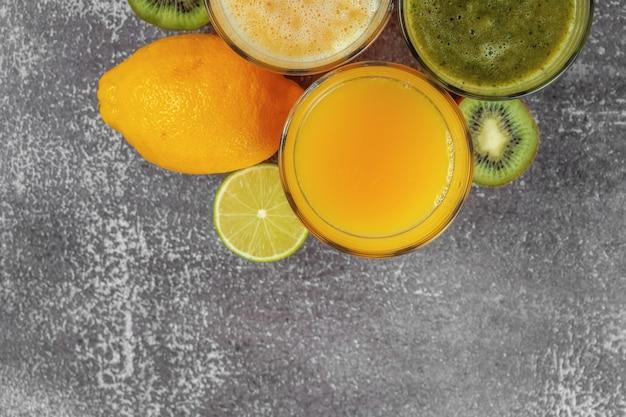 Vista dall'alto di bicchieri di succo d'arancia e banana kiwi e frullati di spinaci con spazio di copia.