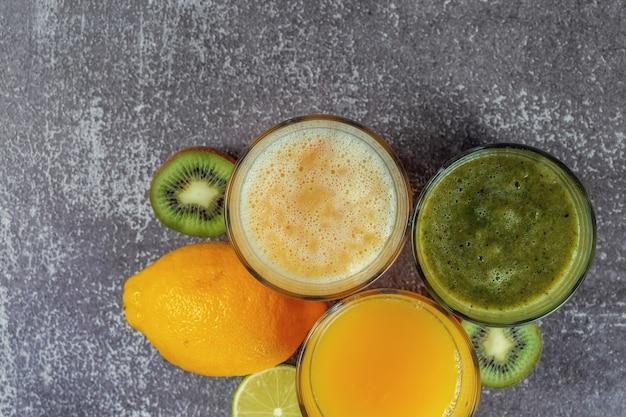 Vista dall'alto di bicchieri di succo d'arancia e banana kiwi e frullati di spinaci.