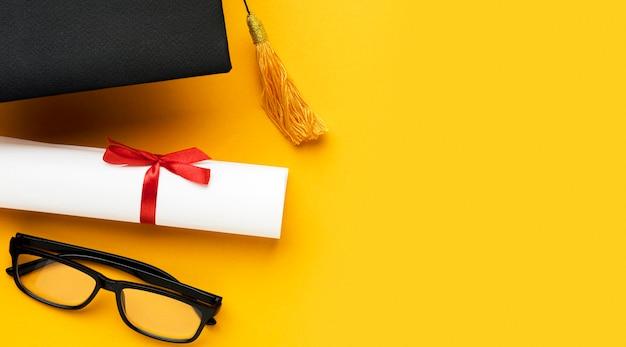 Vista dall'alto di occhiali con cappello accademico e diploma