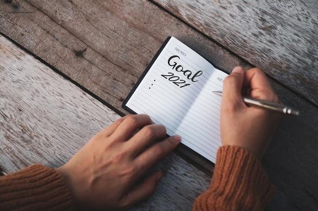 Vista dall'alto dell'obiettivo per il 2021 su carta notebook con penna sul tavolo.