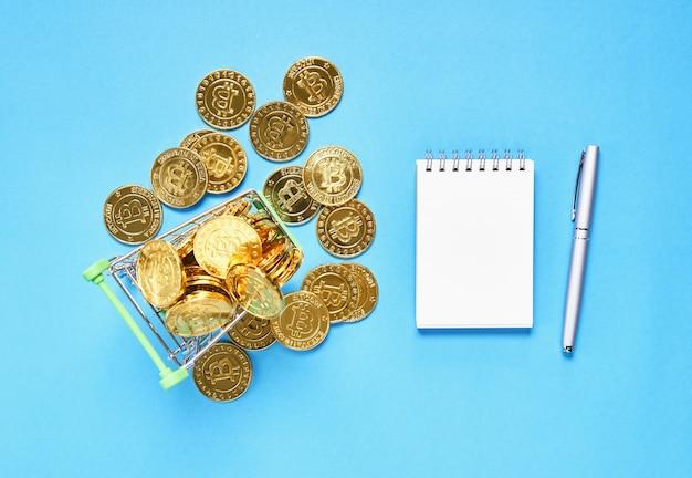 Vista dall'alto, gold bitcoin inserito in un piccolo carrello della spesa. i concetti di valuta digitale possono essere utilizzati per effettuare acquisti online.