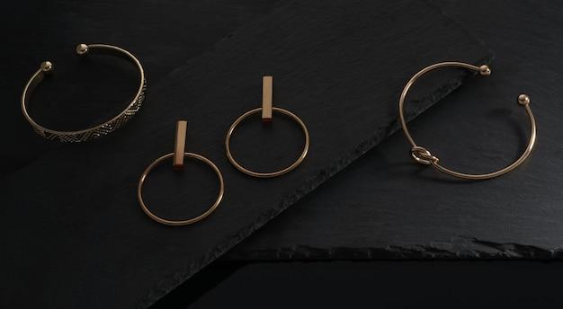Vista dall'alto di bracciali e orecchini dorati accoppiati su lastre di pietra nera con spazio di copia