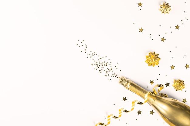Vista dall'alto della bottiglia di champagne dorato con nastro e glitter