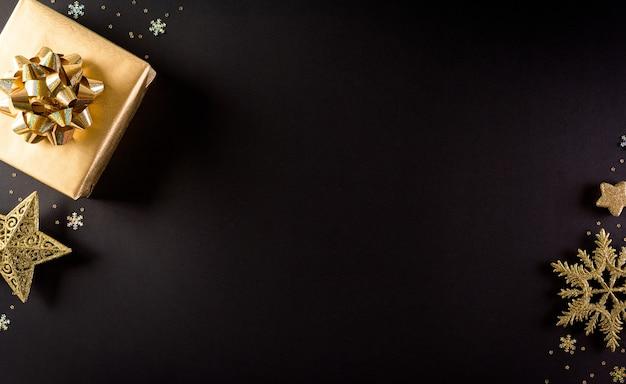 Vista dall'alto di scatole di natale dorate, stella e fiocco di neve su sfondo nero