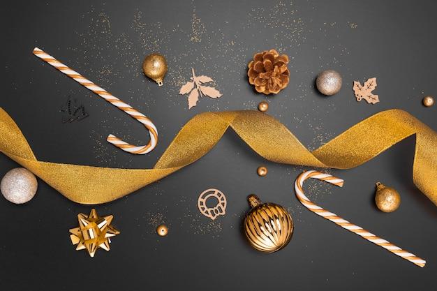 Vista dall'alto di ornamenti natalizi dorati con bastoncino di zucchero e nastro