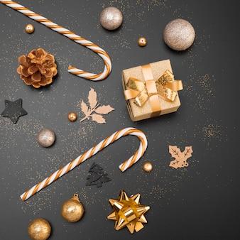 Vista dall'alto di ornamenti natalizi dorati con presente e bastoncini di zucchero