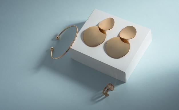 Vista dall'alto di orecchini d'oro e bracciale di diamanti su scatola bianca su sfondo blu con spazio di copia