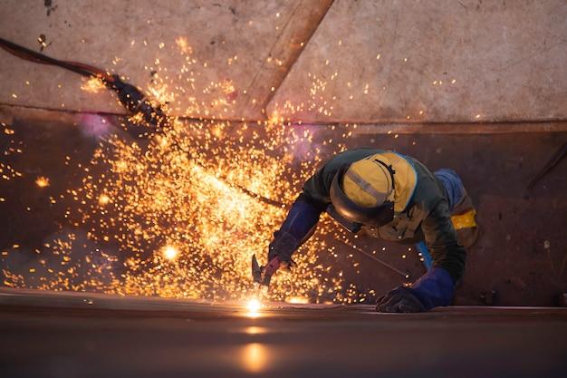 Vista dall'alto scriccatura saldatura scintilla fuoco saldatore industriale indossare maschera protettiva di sicurezza costruzione riparazione serbatoio olio saldatura per la parte in specifiche confinate