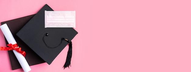 Vista dall'alto del berretto accademico quadrato di laurea con diploma di laurea e maschera isolata su sfondo tavolo rosa.