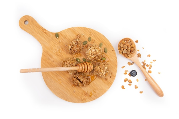 Morsi di granola vista dall'alto con miele su un tagliere di legno e un cucchiaio isolato su sfondo bianco white