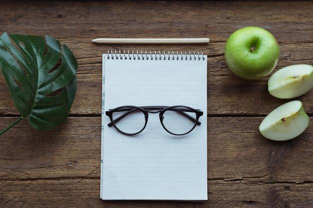 Vista dall'alto di mela verde, blocco note e matita su fondo in legno