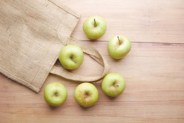 Vista dall'alto di mela verde e borsa della spesa riutilizzabile su fondo in legno