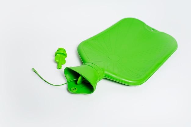 Vista dall'alto della bottiglia di acqua calda medica verde e del cappuccio su sfondo bianco.
