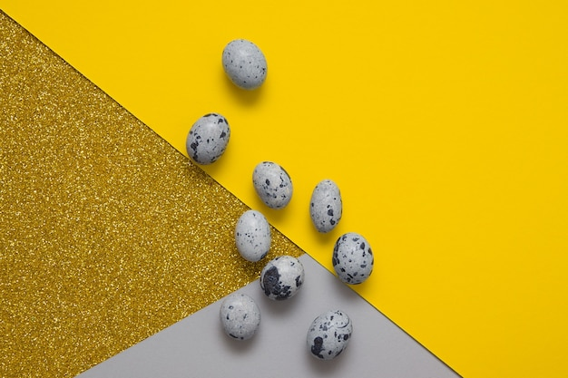 Vista dall'alto uova di pasqua grigie e sfondi di carta colori giallo-grigi