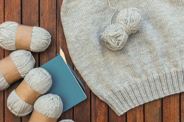 Vista dall'alto di filati per maglieria grigi, taccuino, matita e una parte del maglione lavorato a maglia