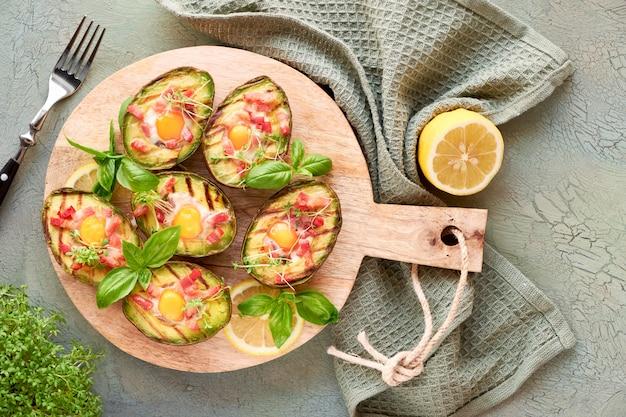 Vista dall'alto su barche di avocado alla griglia con pancetta e uova di quaglia, piatto giaceva su sfondo di legno
