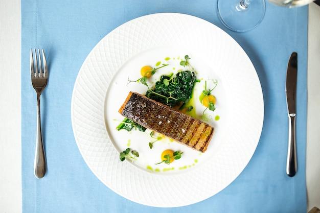 Vista dall'alto sulla bistecca di filetto di salmone alla griglia sul tavolo blu