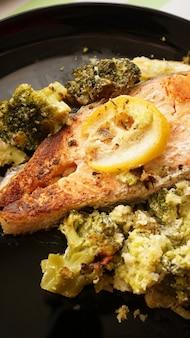 Vista dall'alto della bistecca di salmone alla griglia servita su piastra nera con contorno di verdure di broccoli - verticale