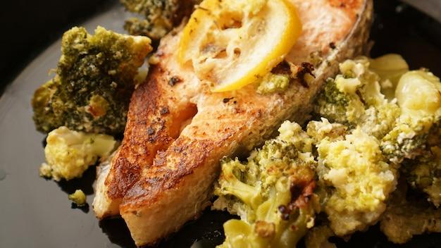 Vista dall'alto della bistecca di salmone alla griglia servita su piatto nero con contorno di verdure di broccoli