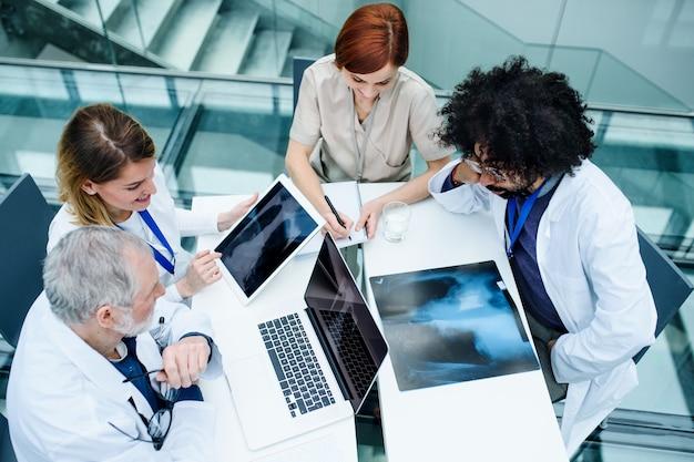 Vista dall'alto di un gruppo di medici che esaminano i raggi x durante una conferenza medica, discutendo problemi.