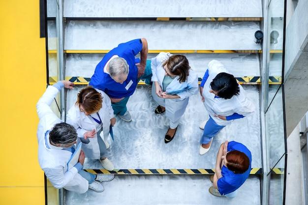 Vista dall'alto di un gruppo di medici in piedi sulle scale in conferenza, parlando.