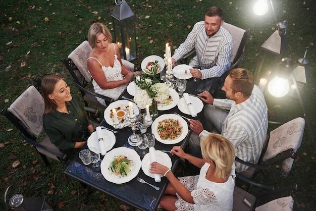 Vista dall'alto di un gruppo di amici in abiti eleganti per una cena di lusso