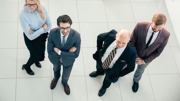 Vista dall'alto. gruppo di specialisti leader in piedi in ufficio