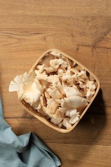 Vista dall'alto un gruppo di funghi ostrica bianca su cesto di vimini su tavolo in legno marrone pronto da cucinare in cucina. copia spazio per il testo