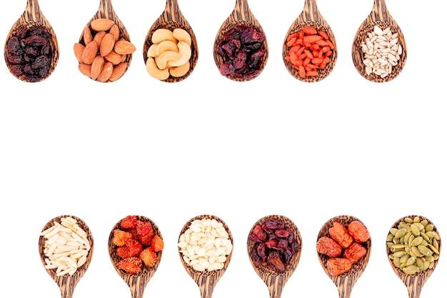 Vista dall'alto gruppo di cereali integrali e frutta secca 12 tipi su cucchiai di legno con spazio copia isolato su sfondo bianco.