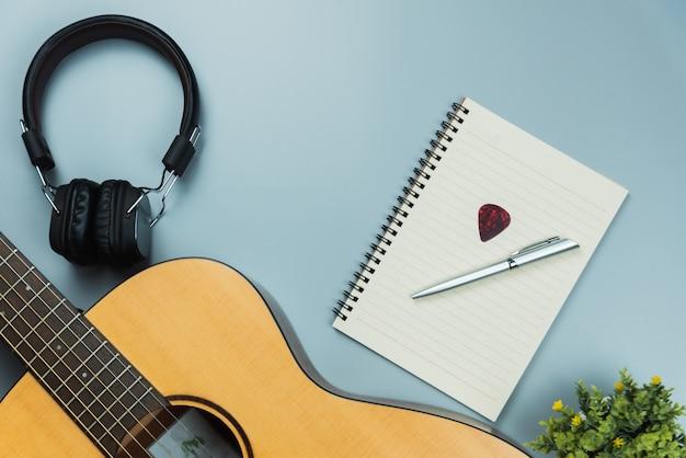 Chitarra di vista superiore e taccuino e cuffia, concetto di musica