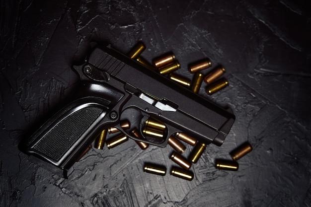 Vista dall'alto di pistole e proiettili di armi da fuoco su sfondo scuro pistola per la difesa o il concetto di attacco di crim...